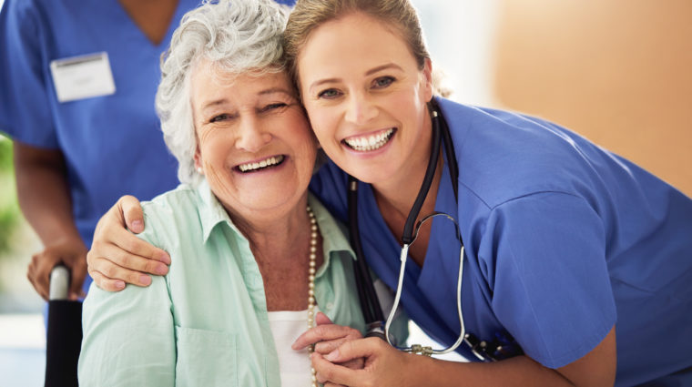 Portrait of a smiling nurse with her senior patient in a hospital